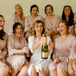 Bride shares a champagne cocktails with her bridesmaids as they wear matching robes and get ready for a fun fall wedding at Morning Glory Farms