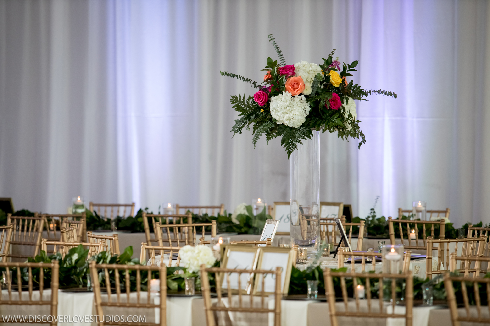 Tall centerpiece with white hydrangeas and brightly colored flowers made by Magnificent Moments Weddings and captured by Discover Love Studios