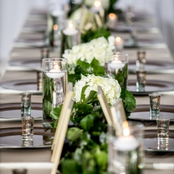 Discover Love Studios captures stunning table setting including gold chargers and garland accented by white hydrangeas created by Magnificent Moments Weddings