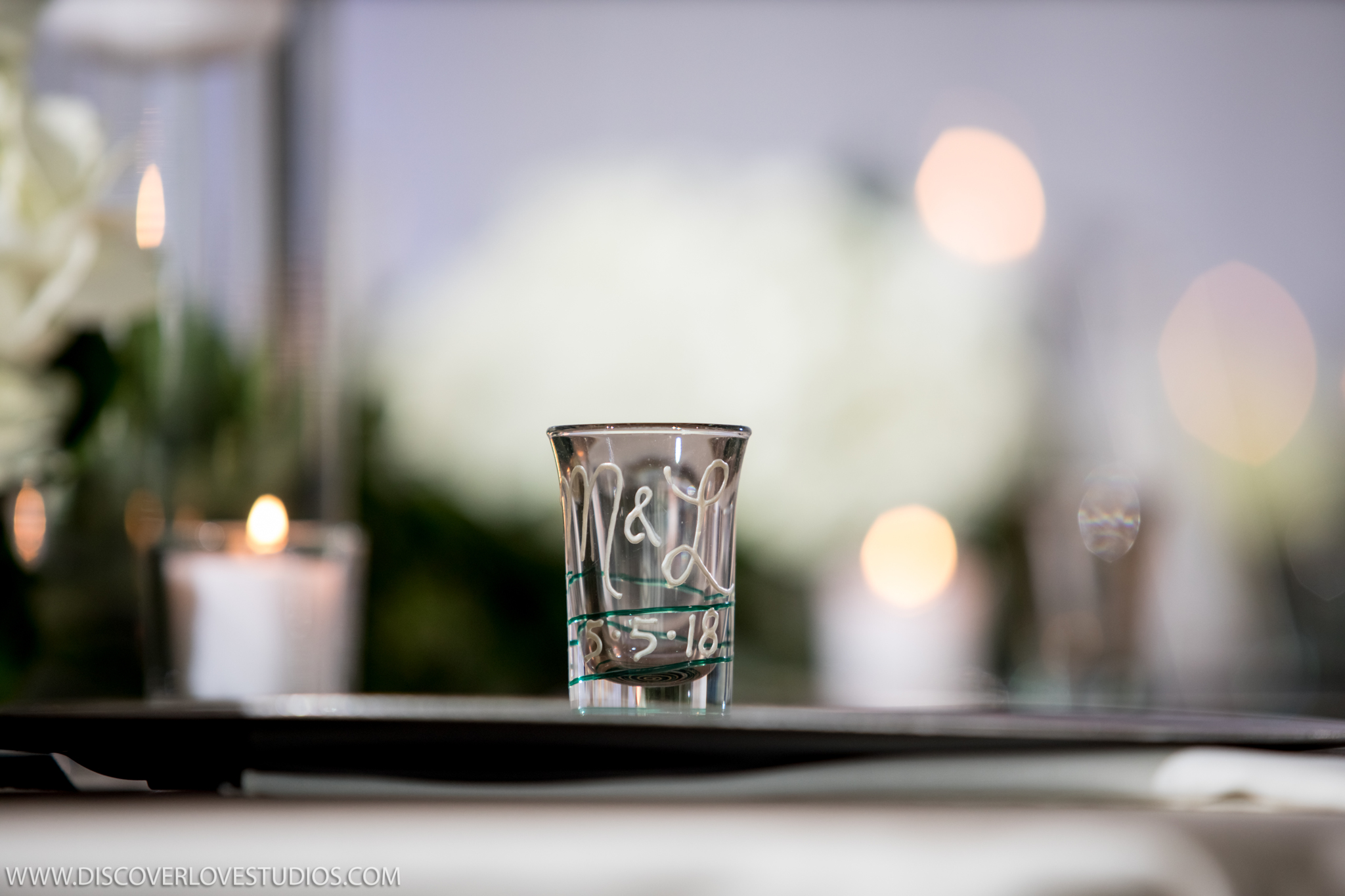 Bride and groom offer custom shot glasses as their guests favors for their wedding reception at The Mint Museum Uptown