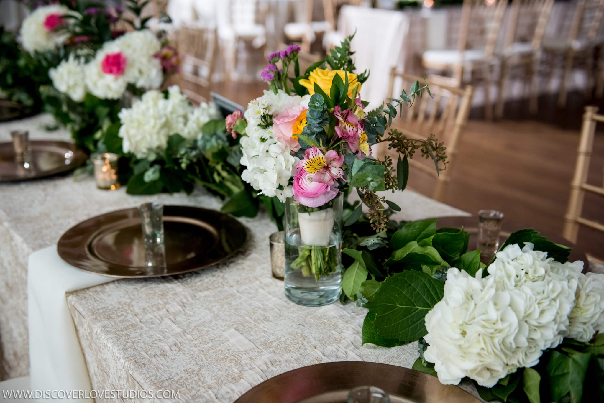 Metallic linens from CE Rentals are accented by gold chargers and colorful florals created by Magnificent Moments Weddings