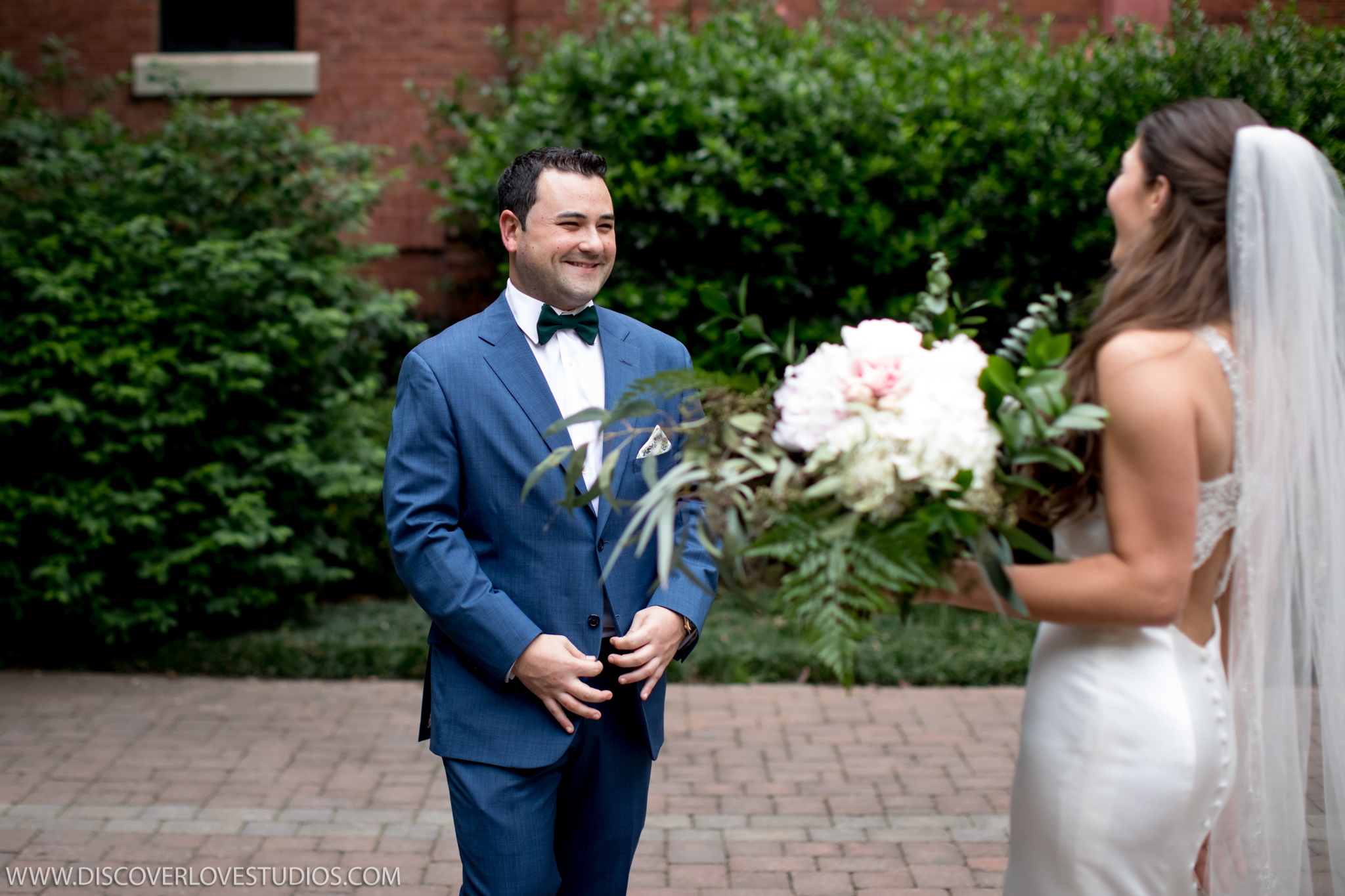 Bride and groom see each other in a first look coordinated by Magnificent Moments Weddings before their Mint Museum Uptown wedding