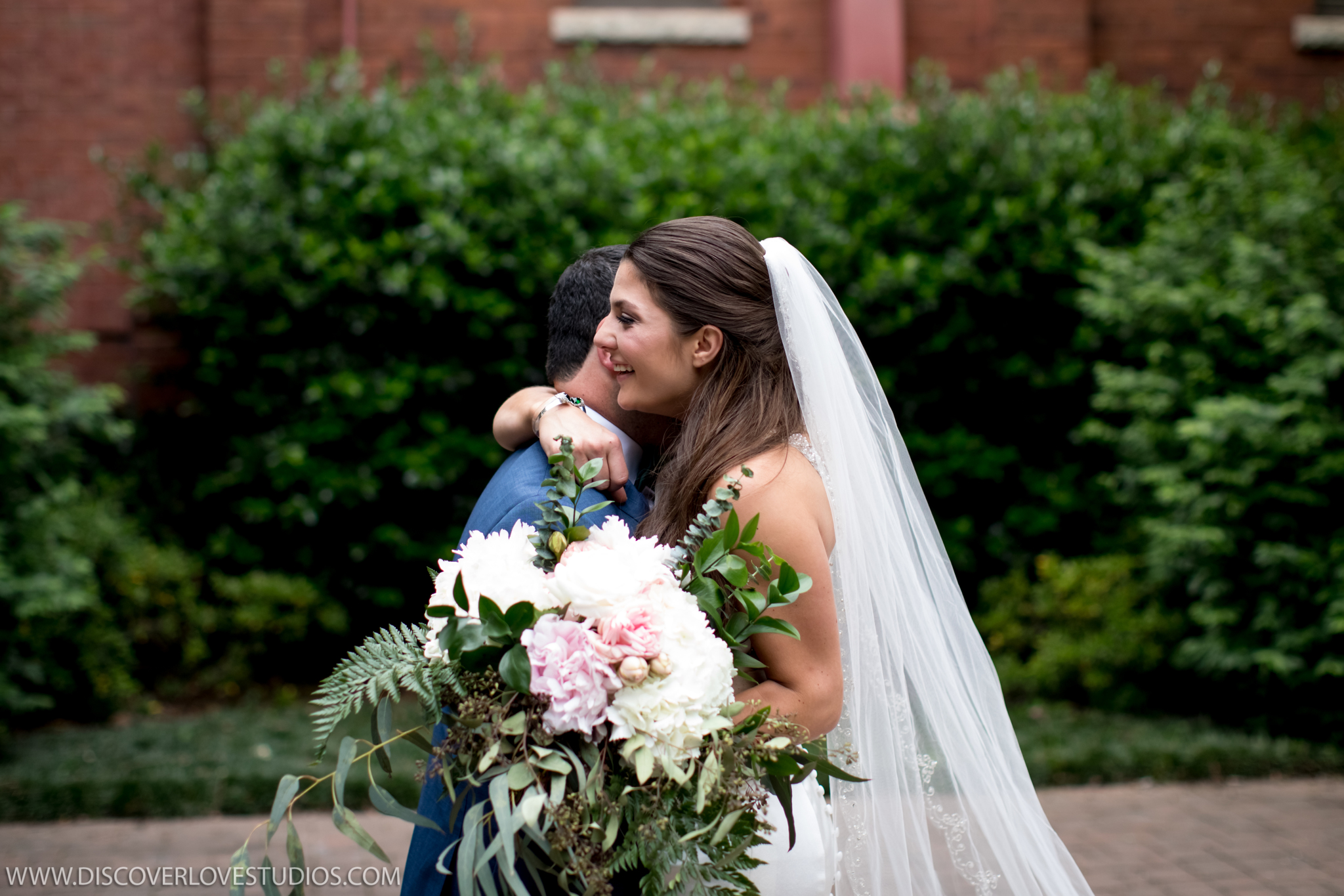 Bride and groom embrace after their first look in Uptown Charlotte captured by Discover Love Studios