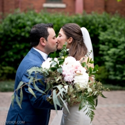 Bride and groom kiss before their wedding ceremony at The Mint Museum Uptown wedding coordinated by Magnificent Moments Weddings