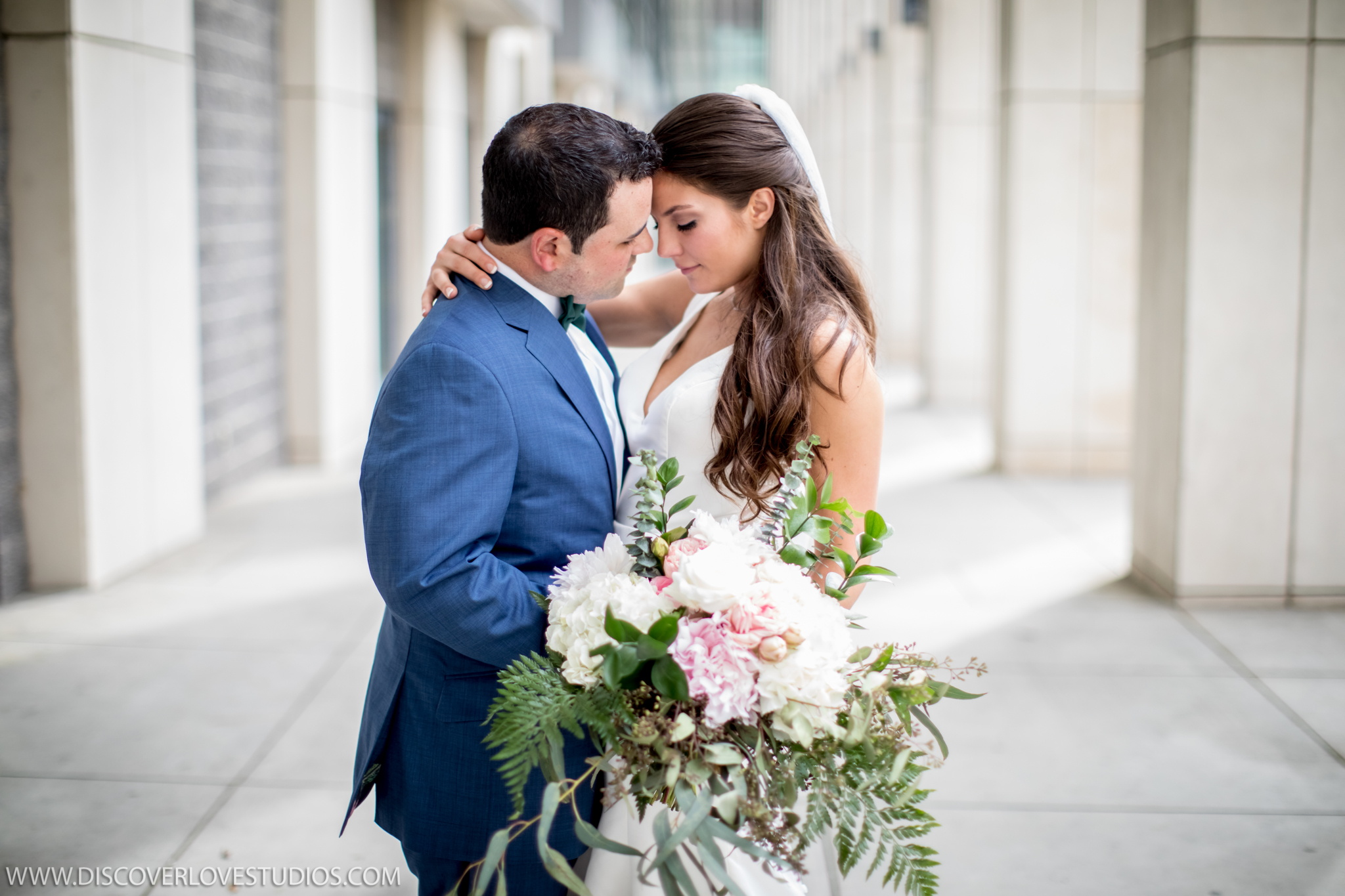 Bride and groom embrace before their uptown wedding at the Mint Museum coordinated by Magnificent Moments Weddings