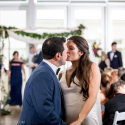 Bride and groom kiss following their wedding ceremony at the Mint Museum Uptown captured by Discovery Love Studios