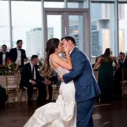 Bride and groom embrace during their first dance at the Mint Museum Uptown ceremony captured by Discover Love Studios