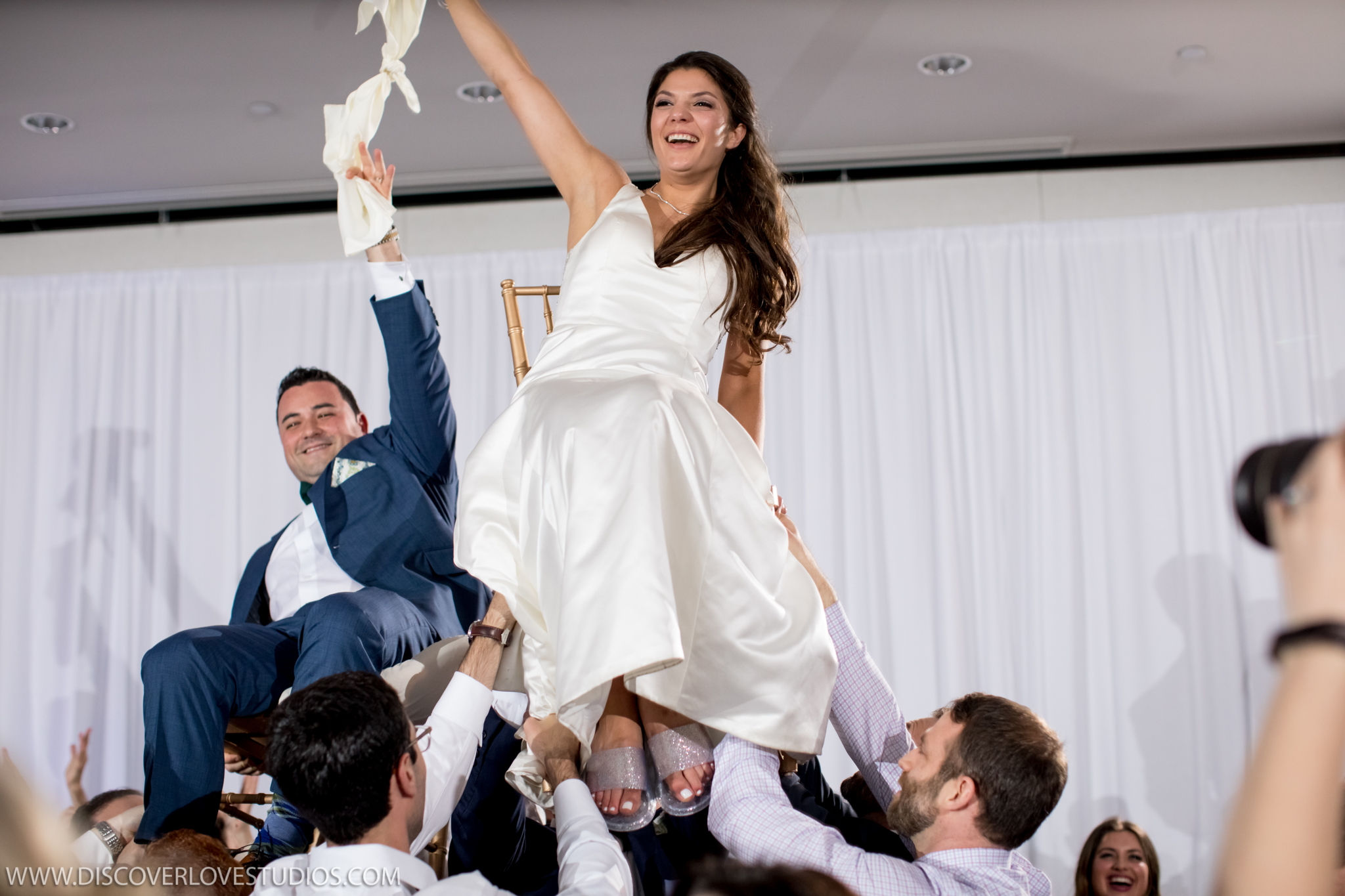 Bride and groom lifted during the hora captured by Discover Love Studios