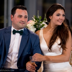 Bride and groom listen to family toasts at their Mint Museum Uptown wedding coordinated by Magnificent Moments Weddings