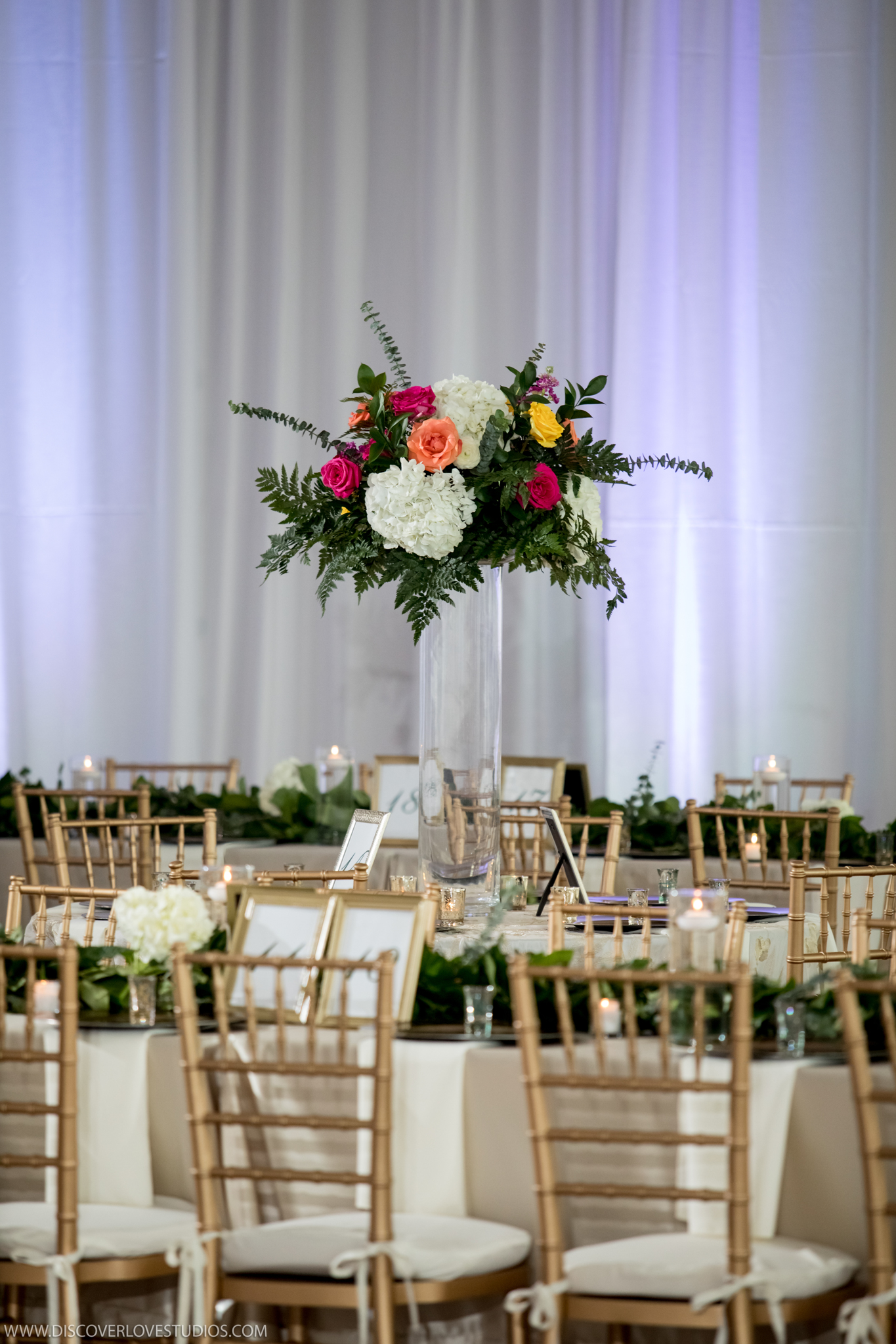 White draping and gold chiavari chairs from CE Rentals create an elegant feel for a Mint Museum Uptown wedding coordinated by Magnificent Moments Weddings