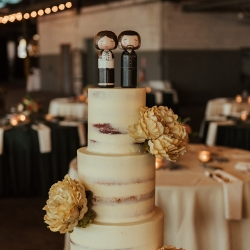 Simple four tiered cake from Saurez Bakery featured custom cake topper depicting the bride and groom