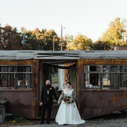 Bride and groom pose before interesting architectural finds on the grounds of Savona Mills during their fall wedding