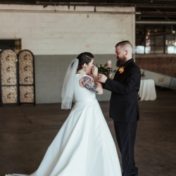 Bride and groom embrace during their fall wedding coordinated by Magnificent Moments Weddings
