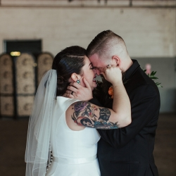 Bride and groom share a sweet moment after exchanging vows during their fall wedding at Savona Mills
