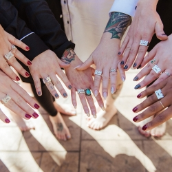 Bride and her bridesmaids show off custom rings before her fall wedding coordinated by Magnificent Moments Weddings
