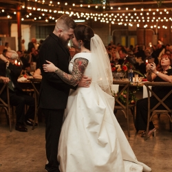 Bride and groom share a romantic first dance under stunning Edison lights installed by Cooke Rentals