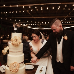 Bride and groom cut a stunning white cake from Suarez Bakery for their fall wedding coordinated by Magnificent Moments Weddings