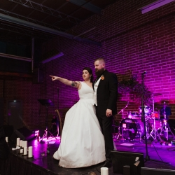 Bride and groom look out over wedding guest on their stage installed by Cooke Rentals during their fall wedding coordinated by Magnificent Moments Weddings