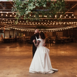 Bride and groom share a private last dance under a stunning greenery hoop designed by Narcisse Greenway Designs