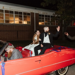 Wedding guests say farewell to the bride and groom as they depart in a vintage red Cadillac from their fall wedding coordinated by Magnificent Moments Weddings