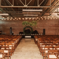 Stunning ceremony space at Savona Mills features lush greenery chandelier and hoop backdrop for a ceremony coordinated by Magnificent Moments Weddings