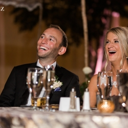 Bride and groom laugh and smile as they are toasted by friends and family all captured by Erin Kranz Photography