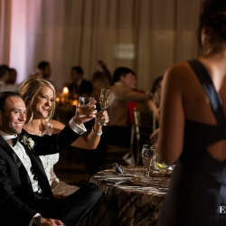 Bride and groom smile and raise a glass as they are toasted by their closet friends and family during their wedding reception coordinated by Magnificent Moments Weddings