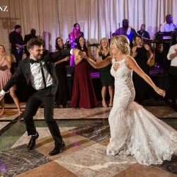 Bride dances with her guests to music by Java Band during her wedding reception coordinated by Magnificent Moments Weddings