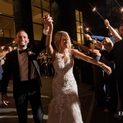 Bride and groom are all smiles as they leave their wedding through a sparkler send off coordinated by Magnificent Moments Weddings