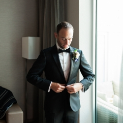 Groom puts on his jacket as he prepares for his Uptown wedding