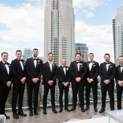 Groom poses with his groomsmen among the Charlotte city skyline during his uptown wedding