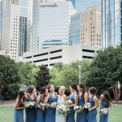 Erin Kranz Photography captures a bride and her bridesmaids among the Charlotte skyline during their Uptown wedding