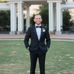 Groom poses in a park in Uptown Charlotte for Erin Kranz Photography on his wedding day