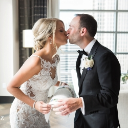 Bride and groom share a kiss after their first look planned by Magnificent Moments Weddings