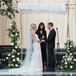 Bride and groom laugh and smile as they marry under a chuppah decorated by Springvine Design