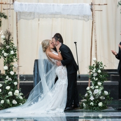 Bride and groom share a kiss after exchanging vows during their wedding ceremony coordinated by Magnificent Moments Weddings
