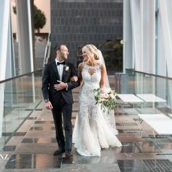 Bride and groom walk among the city skywalk of Founders Hall during their Uptown Charlotte Wedding