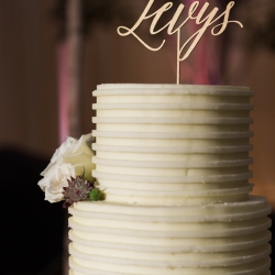 Custom gold cake topper features the couples last name for a wedding reception coordinated by Magnificent Moments Weddings