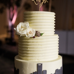 Celestial Cakery designed a stunning five tiered cake featuring the Charlotte city skyline for an Uptown Charlotte wedding