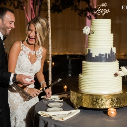 Bride and groom cut an their amazing five tiered cake designed by Celestial Cakery featuring the Charlotte city skyline