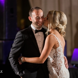 Bride steals a kiss from her husband during their Uptown wedding reception at Founders Hall