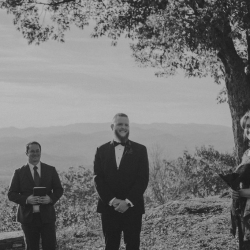 Folk and Wayfarer Photography capture a smiling groom as his brides comes down the aisle of their mountain ceremony at Jump Off Rock