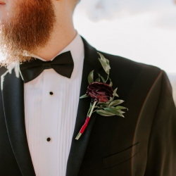 Folk and Wayfarer Photography captures a detail shot of a grooms boutonniere featuring a deep burgundy flower created by Magnificent Moments Weddings