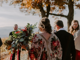 Bride wears a floral shawl during her wedding ceremony at Jump Off Rock captured by Folk and Wayfarer Photography