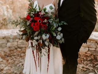 Bridal bouquet features deep burgundy flowers surrounded by a sea of lush greenery created for a mountain wedding by Magnificent Moments Weddings