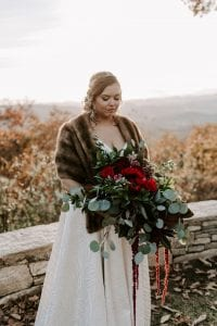Bride holds her bouquet which features burgundy roses and lush greenery accents created by Magnificent Moments Weddings