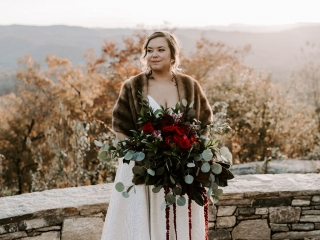 Mountain bride wears a stunning fur shawl before her wedding at Jump of Rock in Asheville, North Carolina