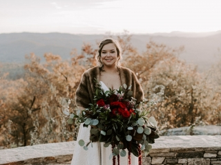 Bride poses in front of the Asheville Mountains holding a stunning bridal bouquet created by Magnificent Moments Weddings