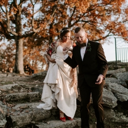 Groom leads his brides down the rocks of the North Carolina Mountains to take in the scenery as they prepare for their wedding designed by Magnificent Moments Weddings