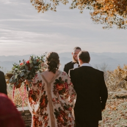 Bride makes her way to a smiling groom and a stunning ceremony space overlooking the North Carolina mountain ranges